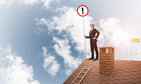 Young businessman with roadsign in hand standing on brick roof. Mixed media Stock Photo