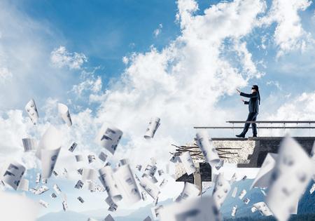 Empresario caminar con los ojos vendados entre papeles volando en el puente de hormigón con gran brecha como símbolo de amenazas y riesgos ocultos. Skyscape y vista de la naturaleza en el fondo. Representación 3D Foto de archivo