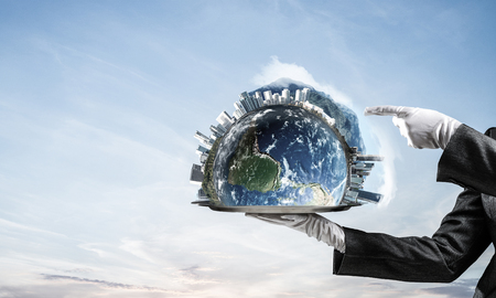 Cropped image of waitresss hand in white glove presenting Earth globe on metal tray and pointing on it with cloudy skyscape on background. 3D rendering. Elements of this image are furnished by NASA. Stock Photo
