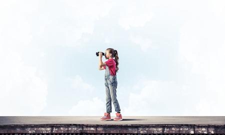 see through: Cute girl of school age on building roof looking in binoculars