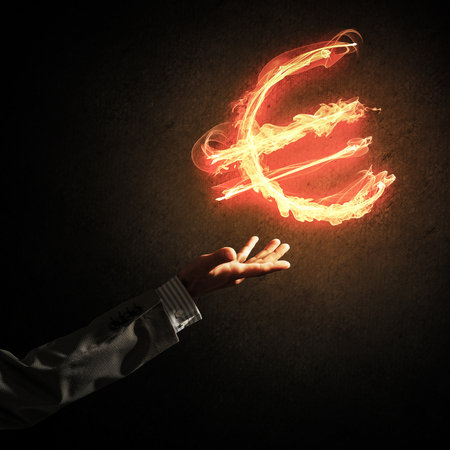 Close of businessman hand pointing at fire glowing euro sign