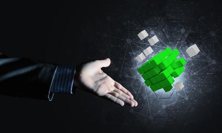 革新、ミクスト メディアのシンボルとしてキューブ フィギュアを持っているビジネスマン手の終了