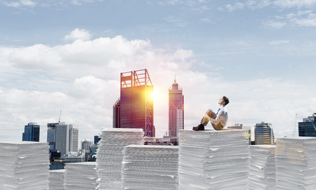 Thoughtful businessman sitting on pile of documents and looking away with cityscape and sunlight on background. Mixed media. Stock Photo