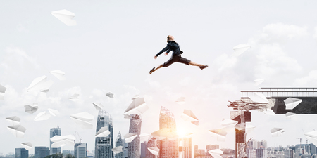 Business woman jumping over gap with flying paper planes in concrete bridge as symbol of overcoming challenges. Cityscape and sunlight on background. 3D rendering. Foto de archivo