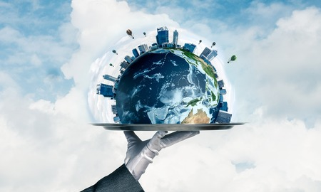 Cropped image of waitresss hand in white glove presenting Earth globe on metal tray with cloudy skyscape on background. 3D rendering. Elements of this image are furnished by NASA.