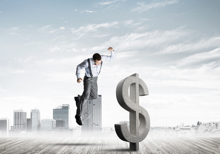 Young furious businessman going to crash with fist stone dollar symbol Stock Photo