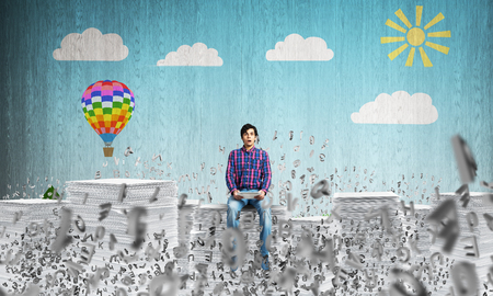 Attractive man in casual clothing sitting among flying letters with sketched landscape view on background. Mixed media.