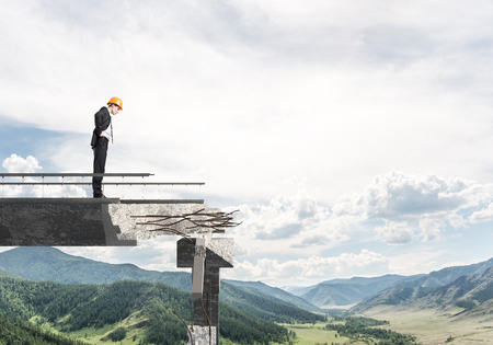 business obstacle: Young engineer in suit and helmet looking down while standing on broken bridge with skyscape and nature view on background. 3D rendering.