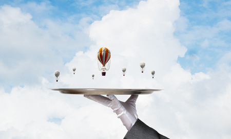 Closeup of waiters hand in glove presenting flying aerostats on metal tray with blue cloudy skyscape on background. 3D rendering.