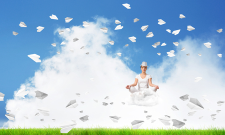Young woman keeping eyes closed and looking concentrated while meditating on cloud among flying paper planes with bright and beautiful landscape on background. Stock Photo