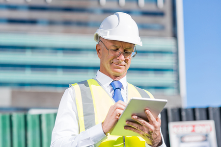Senior ingenieur man in pak en helm werken op tablet pc