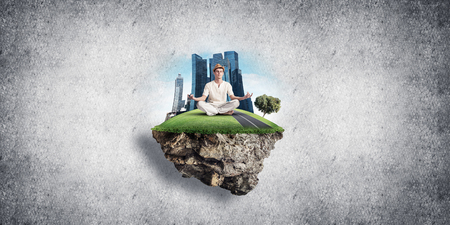 Man in white clothing keeping eyes closed and looking concentrated while meditating on flying island in the air with gray wall on background. 3D rendering.