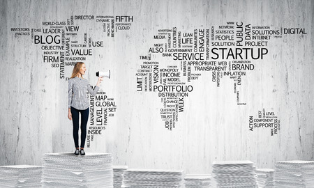 keywords: Woman in casual wear standing on pile of documents with speaker in hand with business-related terms in form of world map on background. Mixed media.