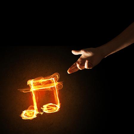 어두운 배경에 사람 손과 화재 음악 기호 닫습니다 스톡 콘텐츠