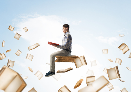Young shocked man floating in blue sky with red book in hands Imagens