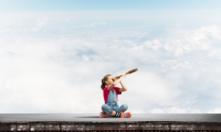 Dziewczynka Cute kid siedzi na dachu domu i patrz? Cw Spyglass Zdjęcie Seryjne