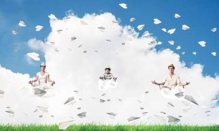Young family keeping eyes closed and looking concentrated while meditating on clouds among flying paper planes with bright and beautiful landscape on background. Stock Photo
