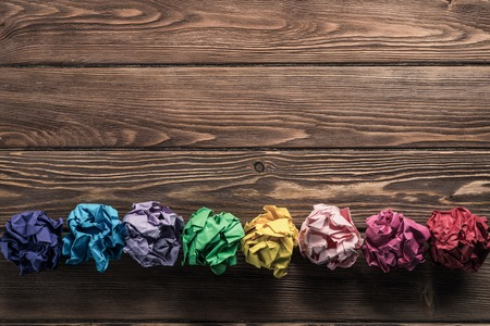 複数のカラフルな crampled 紙のボールのセットは、新しいアイデアの検索の手段として木製のテーブルの行に格納されます。