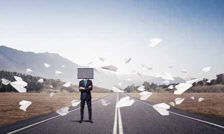 Businessman in suit with TV instead of head keeping arms crossed while standing on the road among flying paper planes with beautiful landscape on background.