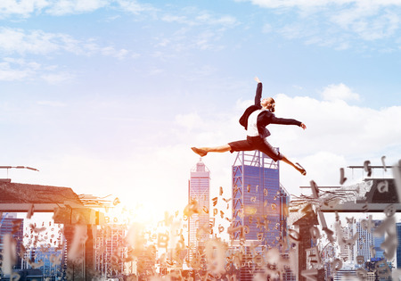 Business woman jumping over gap with flying letters in concrete bridge as symbol of overcoming challenges. Cityscape with sunlight on background. 3D rendering. Stock Photo