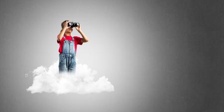 Cute kid girl sitting on cloud and looking in binoculars