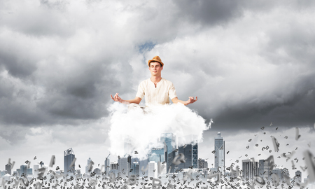 Man in white clothing keeping eyes closed and looking concentrated while meditating on cloud among flying letters with cityscape view on background. Stock Photo