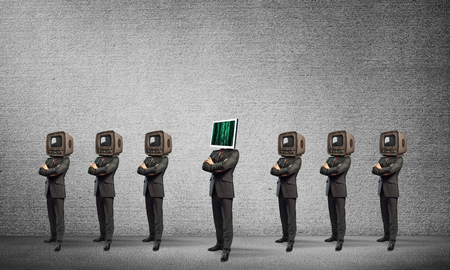 Businessmen in suits with old TV instead of their heads keeping arms crossed while standing in a row and one at the head with monitor in empty room against gray wall on background.
