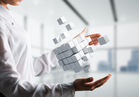 Cropped image of business woman hands holding multiple white cubes in hands with office view background. Mixed media. Stock Photo
