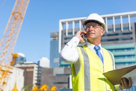 Engenheiro sênior, homem, em, paleto, e, capacete, falando, telefone móvel Foto de archivo - 90265888