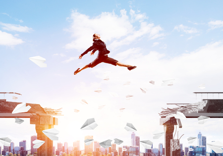 Business woman jumping over gap with flying paper planes in concrete bridge as symbol of overcoming challenges. Cityscape with sunlight on background. 3D rendering. Stock Photo