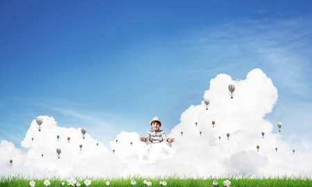 Young little boy keeping eyes closed and looking concentrated while meditating on cloud among flying aerostats with bright and beautiful landscape on background. Stock Photo