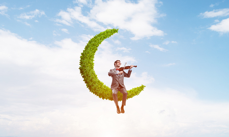 Young man wearing suit and glasses sitting on green moon and playing violin