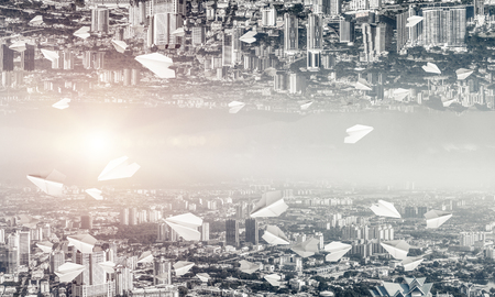 Abstract image of two modern urban worlds located among flying paper planes and upside down to each other on the sky background. Wallpaper, backdrop with copyspace.