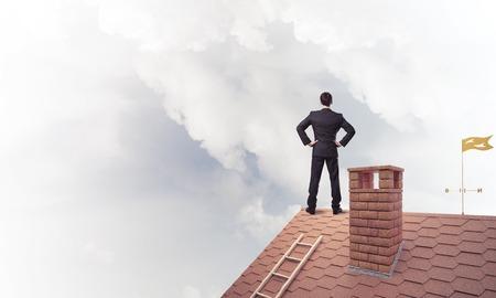 若いビジネスマンの家の屋根に立って、よそ見を決定されます。ミクスト メディア