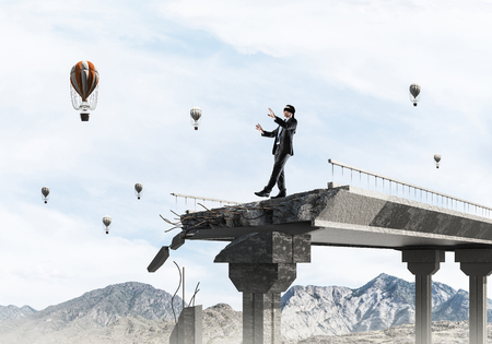 Businessman walking blindfolded on concrete bridge with huge gap as symbol of hidden threats and risks. Flying balloons and nature view on background. 3D rendering. Stock Photo