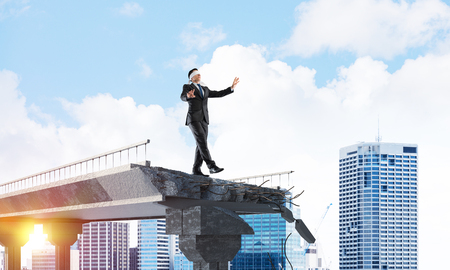 Businessman walking blindfolded on concrete bridge with huge gap as symbol of hidden threats and risks. Cityscape and sunlight on background. 3D rendering. Banco de Imagens