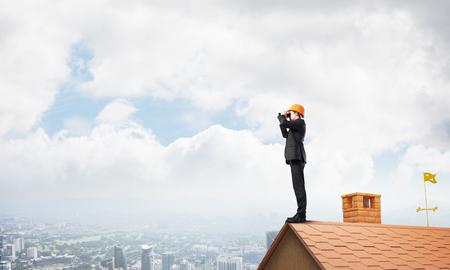 Jonge zakenman in pak en helm op dakrand op zoek naar iets nieuws. Gemengde media