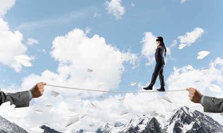Businessman walking blindfolded on rope among flying paper planes and above high mountains as symbol of hidden threats and support. Nature view on background.