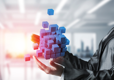 Cropped image of business woman hands holding multiple blue cubes in hands with sunlight on office background. Mixed media.