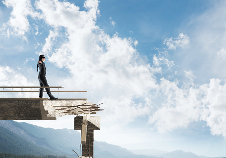 Businessman walking blindfolded on concrete bridge with huge gap as symbol of hidden threats and risks. Skyscape and nature view on background. 3D rendering. Foto de archivo