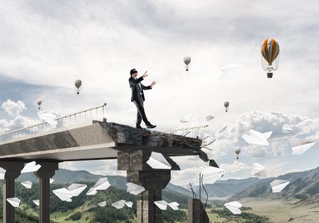 Empresario caminando con los ojos vendados entre volar aviones de papel en el puente de hormigón con gran brecha como símbolo de amenazas y riesgos ocultos. Globos voladores y vista de la naturaleza en el fondo. Representación 3D