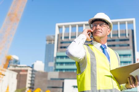 Senior engineer man in suit and helmet talking mobile phone Stock fotó