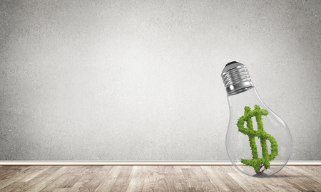 Glass lightbulb with green dollar symbol inside in empty room with grey wall on background. 3D rendering. Stock Photo
