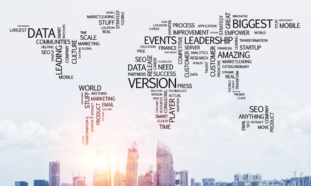 Business-related terms collage in form of world map with modern cityscape and sunlight on background.
