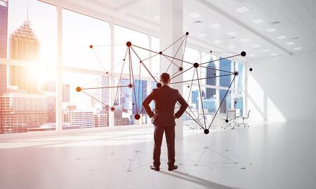 Elegancki biznesmen w nowoczesne wnętrza biurowe i koncepcja połączenia społecznego. Różne środki przekazu Zdjęcie Seryjne