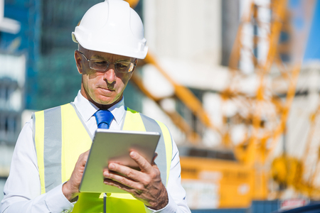 Senior engineer man in suit and helmet working on tablet pc Stock Photo