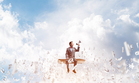 Young businessman sitting on books and screaming emotionally in megaphone Stock Photo