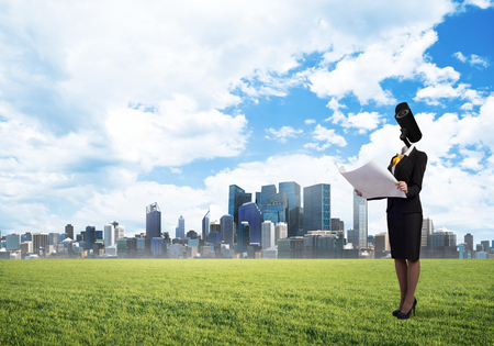 Elegant businesswoman outdoors with papers in hands and camera instead of head Stock Photo