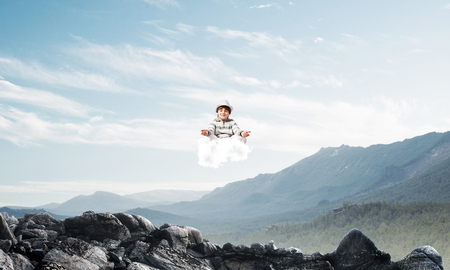 Young little boy keeping eyes closed and looking concentrated while meditating on cloud in the air with beautiful and breathtaking landscape on background.