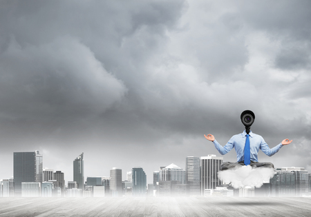 Elegant businessman outdoors floating on cloud and camera instead of head Banque d'images